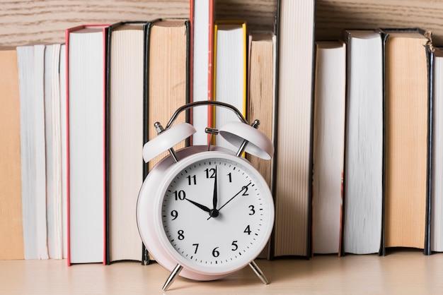 Белый будильник, показывающий 10 часов перед книжной полкой на деревянном столе