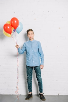 カラフルな風船を手で押し10代の少年の肖像画