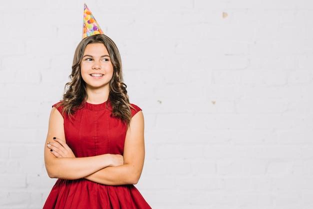 レンガの壁に立っている赤いドレスで微笑んでいる10代の少女の肖像画