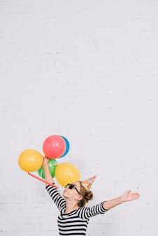 パーティーホーンを吹く白いレンガの壁に立っている10代の少女