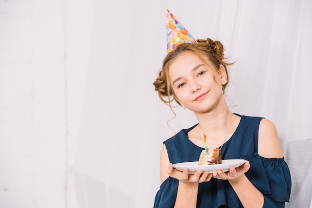 白い皿にケーキのスライスを保持している10代の少女の肖像画