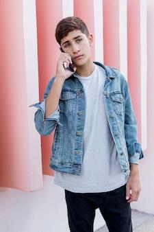 ピンクの壁の前に立っている携帯電話で話しているハンサムな10代の少年