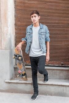 スケートボードを保持している閉じた段ボール鉄サイディングの前に立っている10代の少年の肖像画