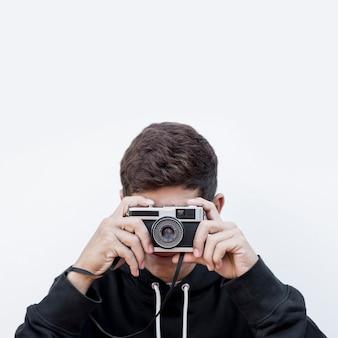 写真を撮る10代の少年のクローズアップホワイトバックグラウンドに対してレトロなビンテージ写真カメラをクリックします