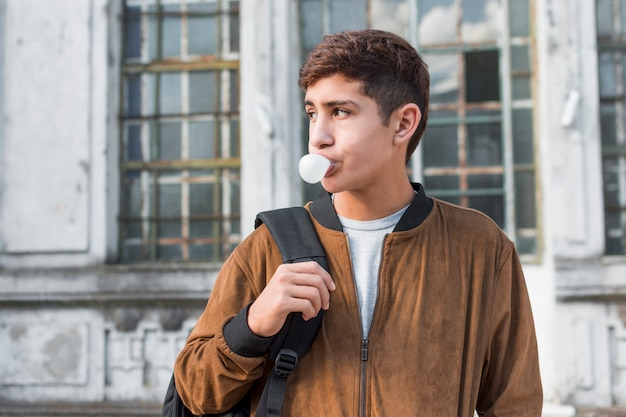 屋外でバブルガムを吹く10代の少年のクローズアップ
