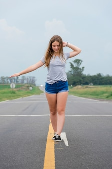 空の路上で踊る魅力的な10代の現代少女
