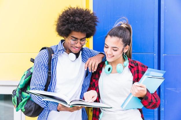 一緒に勉強して青と黄色の壁に対して多様な10代のカップルに立って