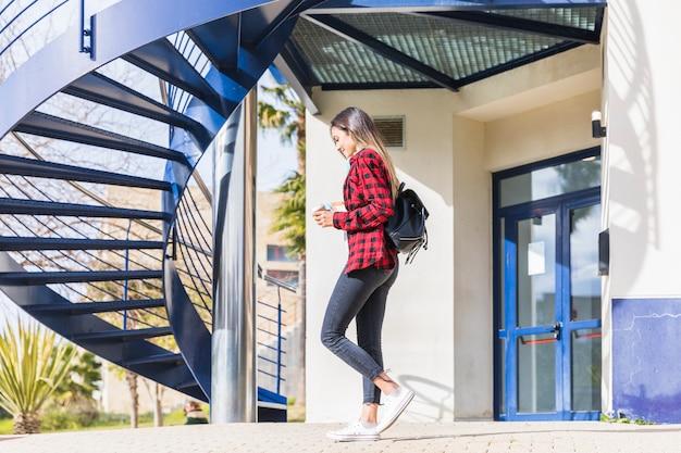 大学の建物の前を歩いて10代女子学生の側面図