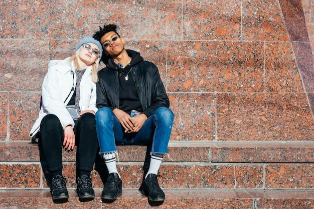 屋外で一緒に座っているファッショナブルな10代のカップル