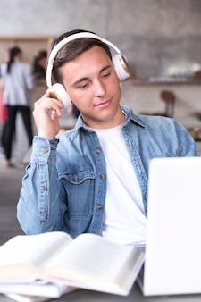 教室のテーブルに座っているヘッドフォンで10代の少年