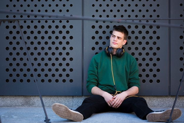 床に座って、広げられた足でもたれかかってヘッドフォンを持つ男性10代