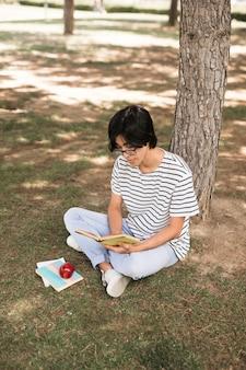アジアの10代学生の木の下で本を読んで