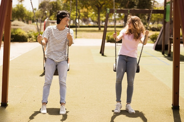 遊び場で揺れている10代の若者の多民族のカップル