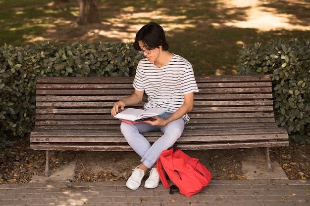 アジアの10代の男がベンチの教科書
