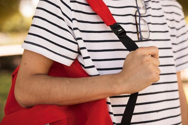 10代の学生が肩にバックパックを運ぶ