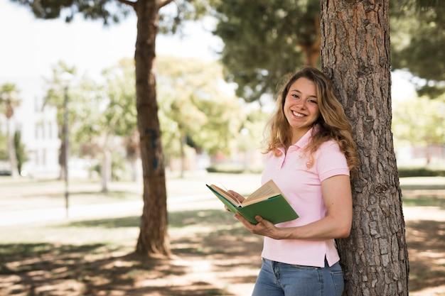 若い10代の女の子が公園で本を読んで