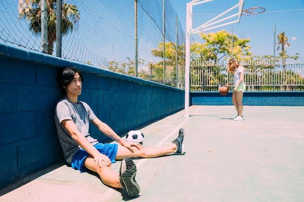 スポーツグラウンドフェンスの横に休んでいるアジアの10代学生