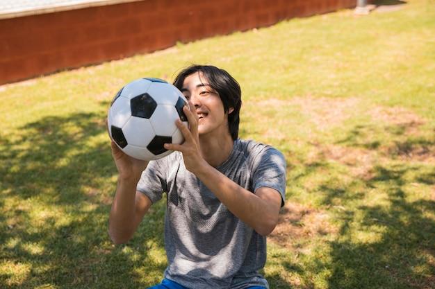 陽気な10代のアジアの学生がサッカーボールを引く