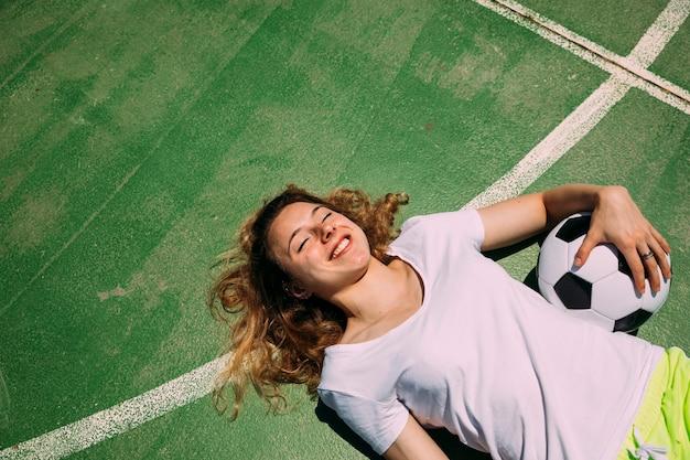 陽気な10代学生、サッカー場で横になっています。