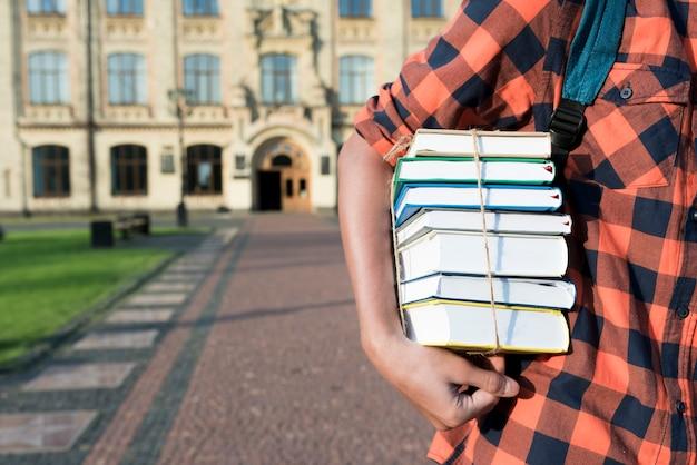 彼の腕の下で本を持っている10代の少年のクローズアップ