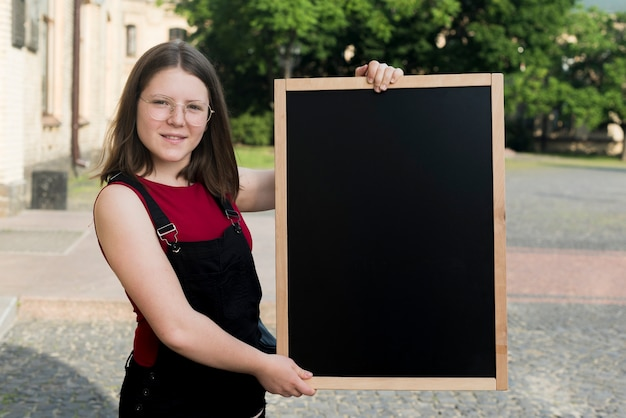 手で黒板を保持している10代の少女のミディアムショット