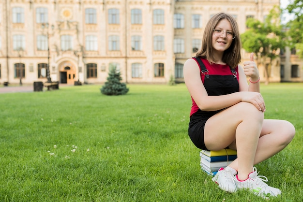 高校の前で本に座っている10代の少女