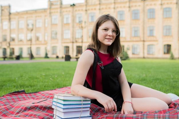 高校の前で毛布の上に座っている10代の少女