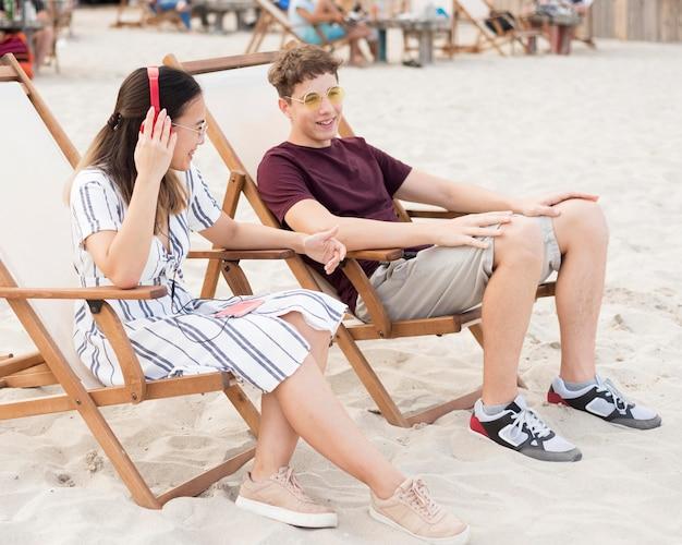 10代の若者がビーチで一緒に身も凍るよう