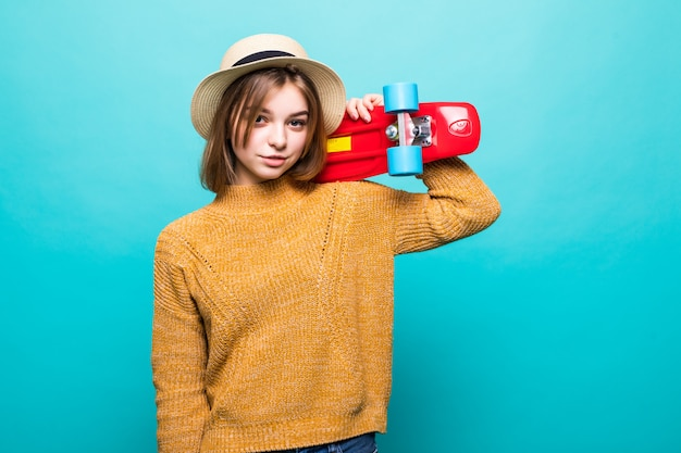 緑の壁の上に孤立して立っている間サングラスと帽子スケートボードを保持している帽子の若い10代女性の肖像画