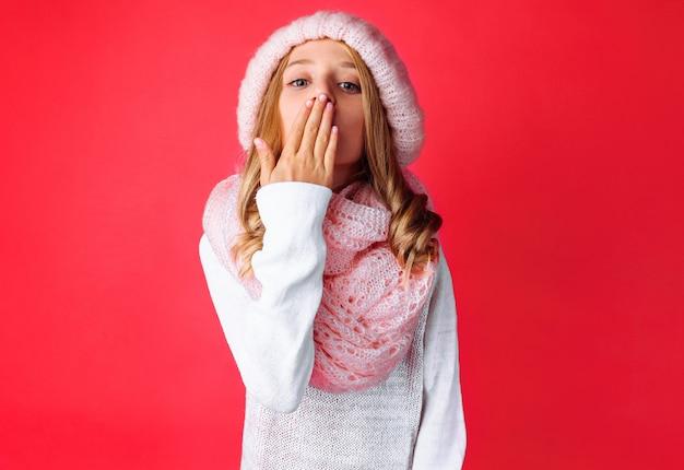 白いセーターを着たかわいい10代の少女がキスを送信します
