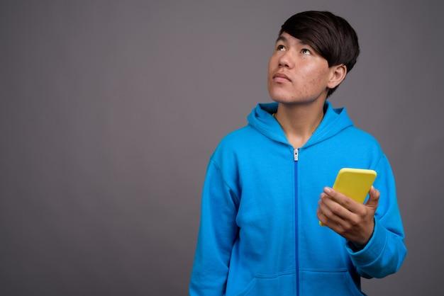 灰色の壁に青いジャケットを着ている若いアジアの10代の少年
