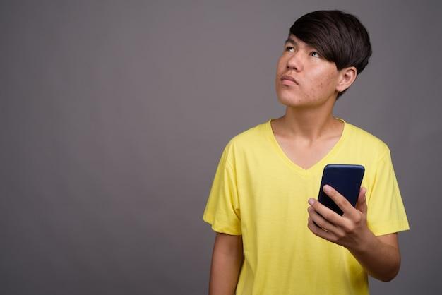 灰色の背景に対して黄色のシャツを着ている若いアジアの10代の少年