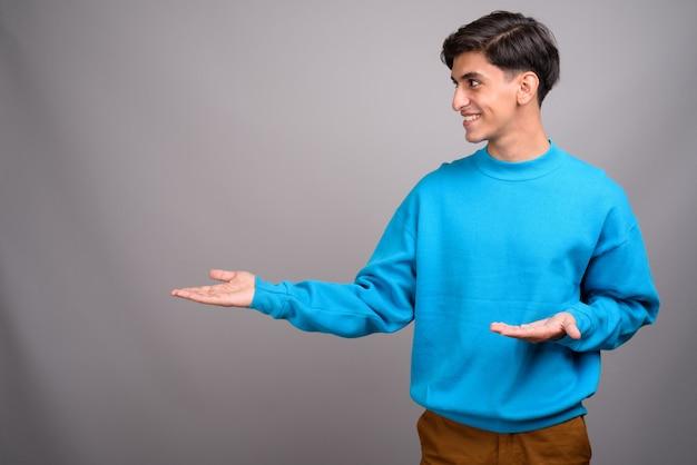 灰色の背景に対して若いハンサムなペルシャの10代の少年のスタジオ撮影