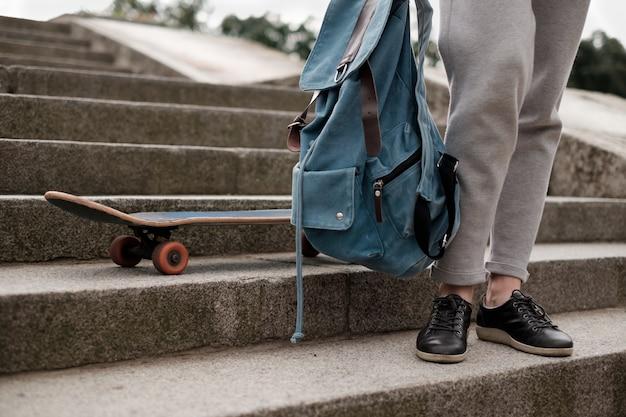 彼女のスケートの近くの階段にバックパック立って10代の女の子
