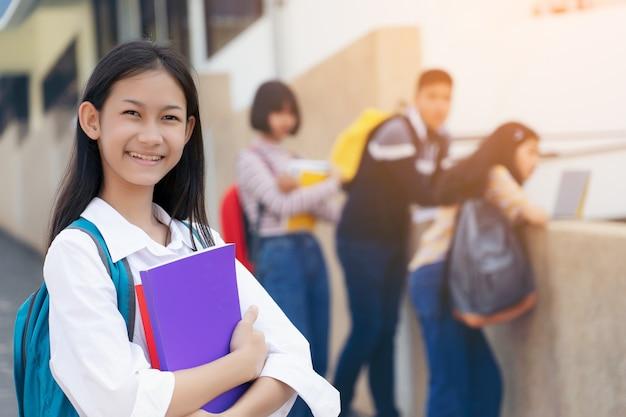 バックグラウンドで友達とノートを保持しているカバンを運ぶ若い学生10代の女の子高校生