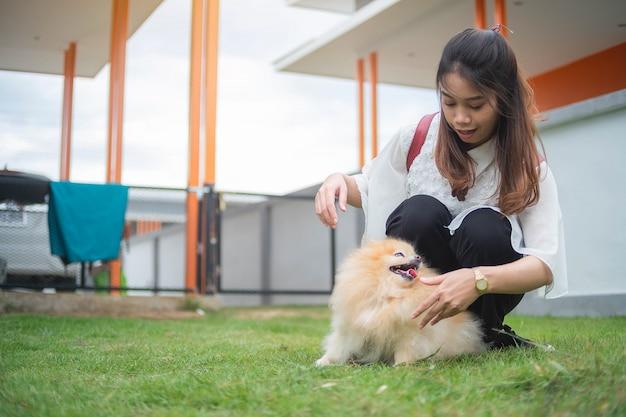 アジアの女性の家でポメラニアン犬と遊ぶ10代女性