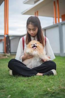 アジアの女性の家でポンペラ犬と遊ぶ10代女性が屋外でリラックスします。