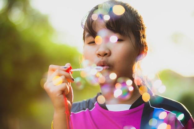 アジアの10代の美しい太陽の光に対してスープ泡でリラックス