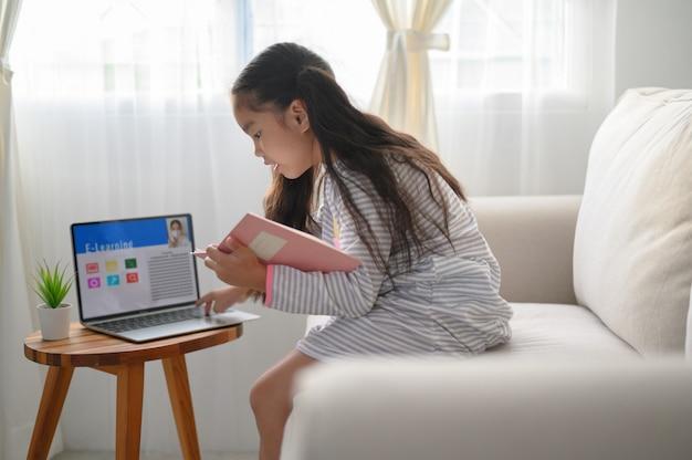 宿題を書いて、テーブルに座っている女子学生。ラップトップコンピューターを使用して勉強する10代。新しい正常。社会的距離。家にいる。