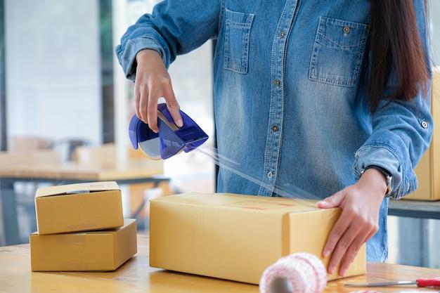 10代の少女が製品を箱に詰め、透明な粘着テープを使用して顧客に届けています。