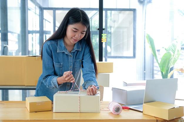 10代の少女が製品を箱に詰め、ロープを使って顧客に届けています。