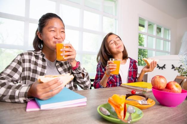 10代の女の子は学校に行く前に、朝食を食べることを楽しむ、学校のコンセプトに戻る