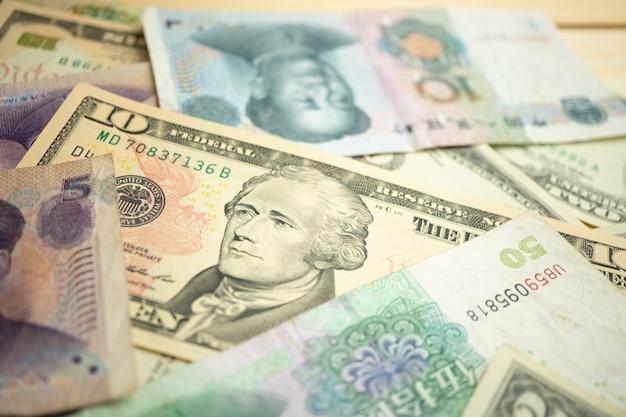 Выберите фокус стопки 10 долларов сша под банкнотой китайского юаня.