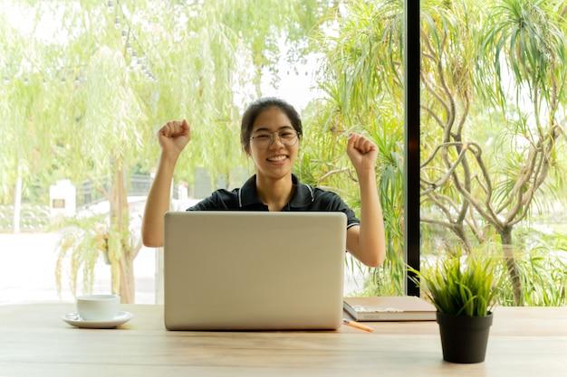 アジアの10代の陽気がネットブックの前で祝う成功を興奮させた