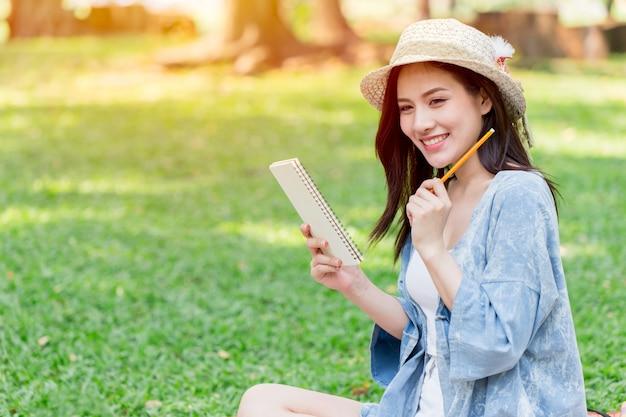 アジアの10代の笑顔が公園でメモスクリプトの手紙を書く