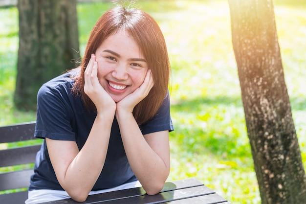 彼女の頭を保持している手でアジアの10代の笑顔