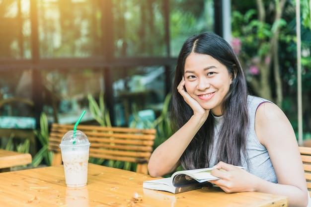 本を読んでリラックスタイムをお楽しみください、コーヒーショップヴィンテージ色のトーンの本でアジアの女性のタイの10代の笑顔