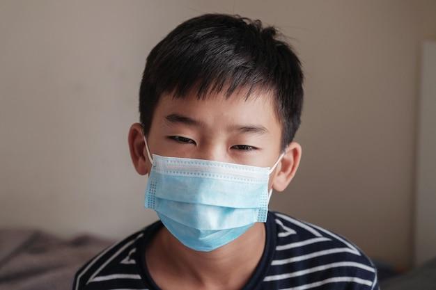 マスクを身に着けている病気のプレティーン10代のアジアの少年のヘッドショット肖像画