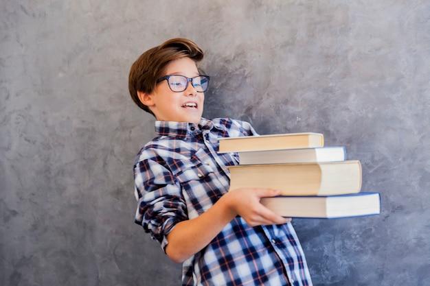 本を保持しているかわいい10代の学校の少年