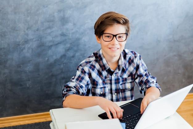 自宅のラップトップに取り組んでいる10代の少年